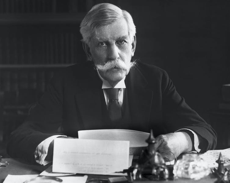 Oliver Wendell Holmes, gray haired and with a big mustache, sitting at a desk.