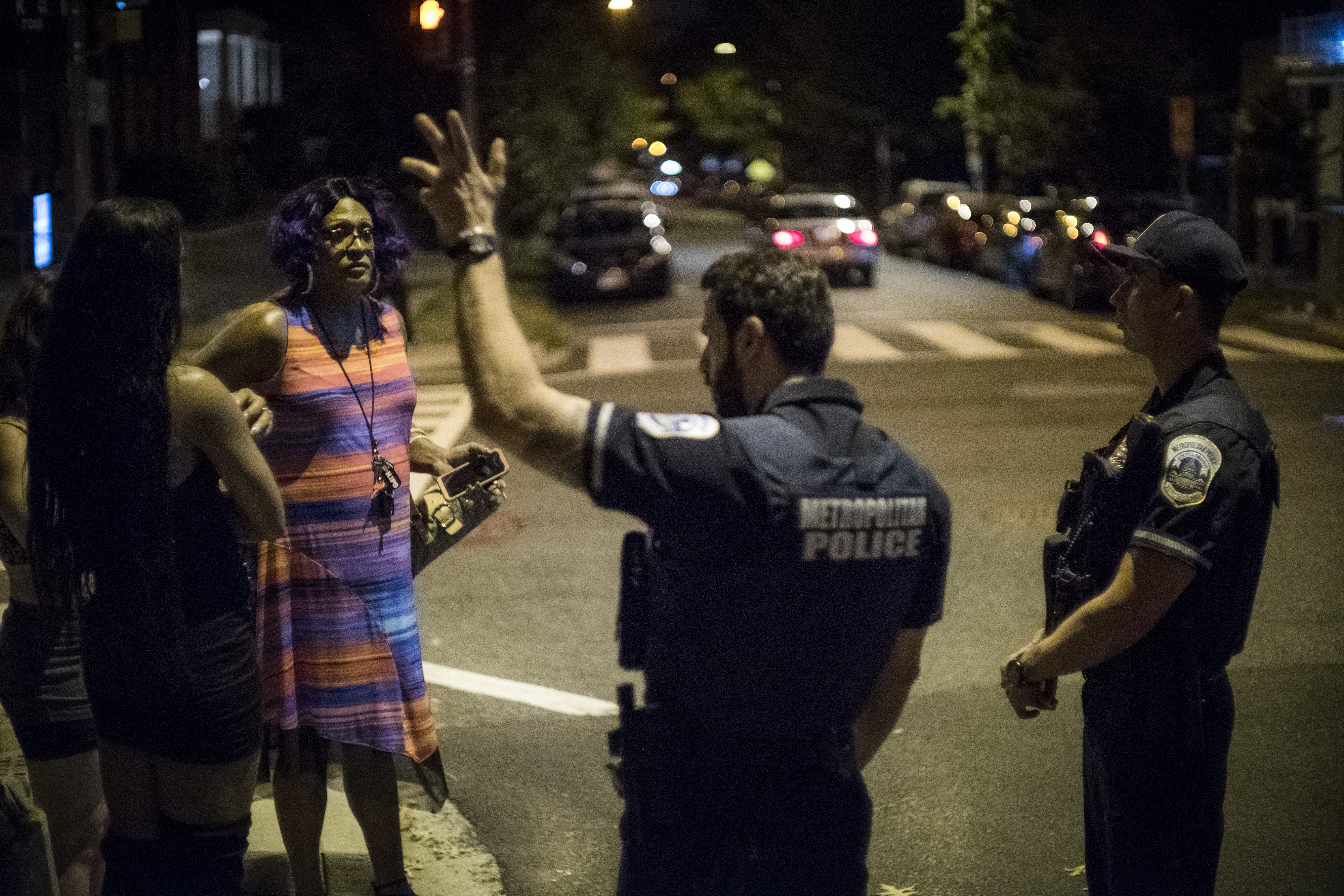 A woman talks with two police officers on a street at night
