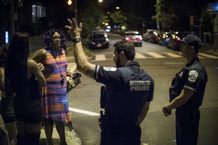 Женщина разговаривает с двумя полицейскими на улице ночью