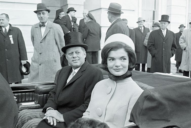 Jackie Kennedy rides in a car alongside John F. Kennedy.