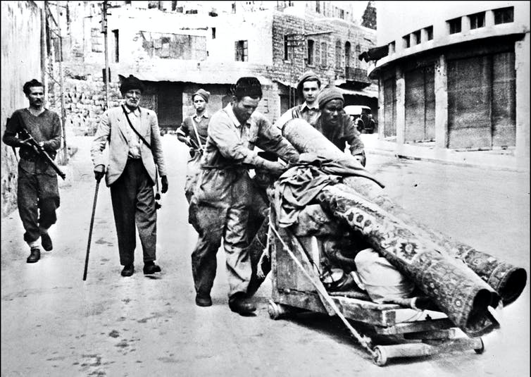 A black-and-white image shows two men pushing a wooden cart of belongings through a city street. An armed man follows them.