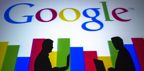 The silhouettes of two people using laptops are seen against the Google logo.