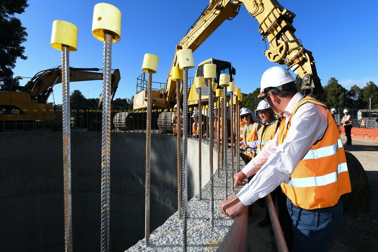 government ministers in high-viz vests and hard hats inspect work on construction project