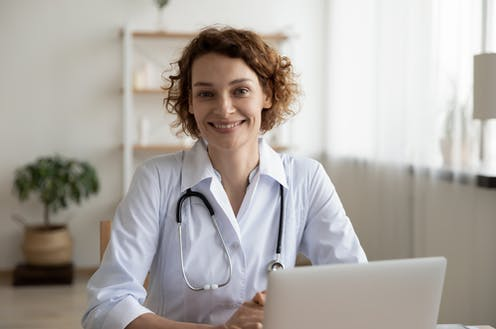 Female GP with stethoscope smiling
