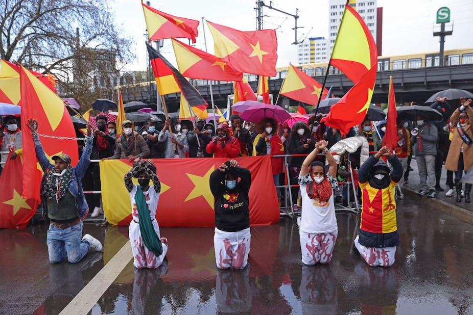 Protestors kneel in front of Tigrayan flags