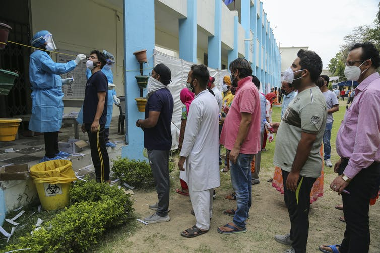 People lining up to receive a COVID test in India.