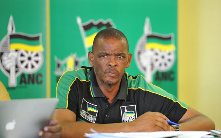 A man sitting in a chair and wearing a golf shirt in ANC colours looks in the distance.