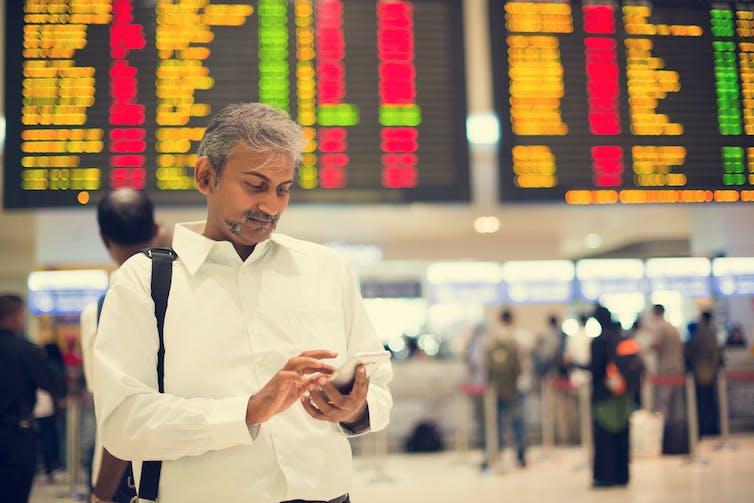 Un hombre de origen indio comprobando su teléfono en un aeropuerto