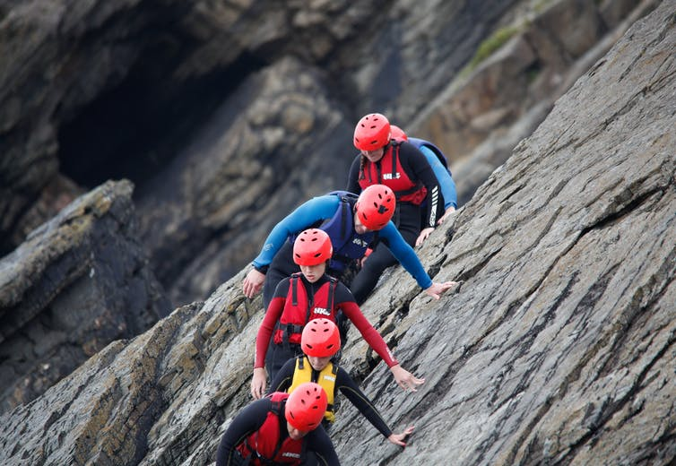 chlidren in red helmets and wetsuits climb down a cliff