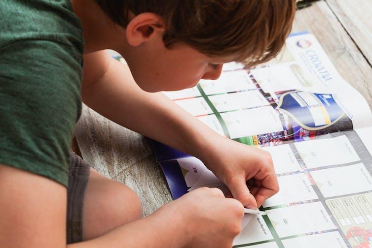 A child putting a football sticker into an album.