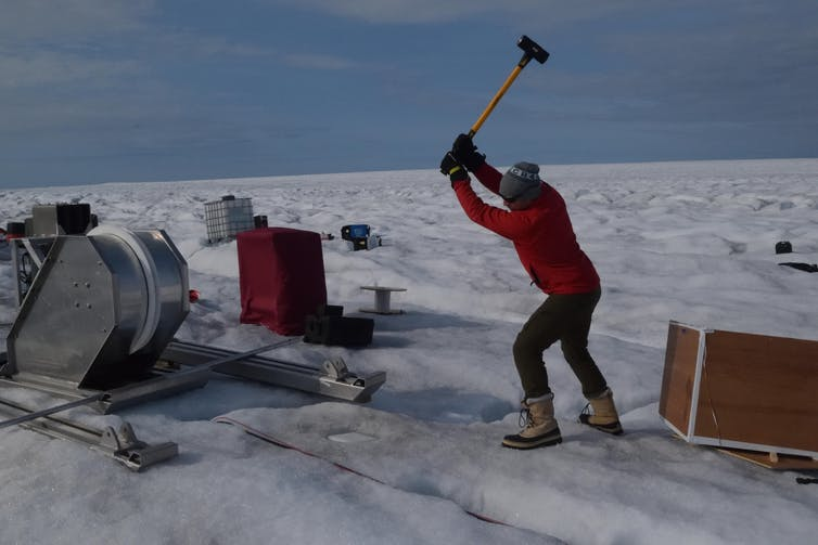 A man raises a hammer above an icy tundra surrounded by equipment