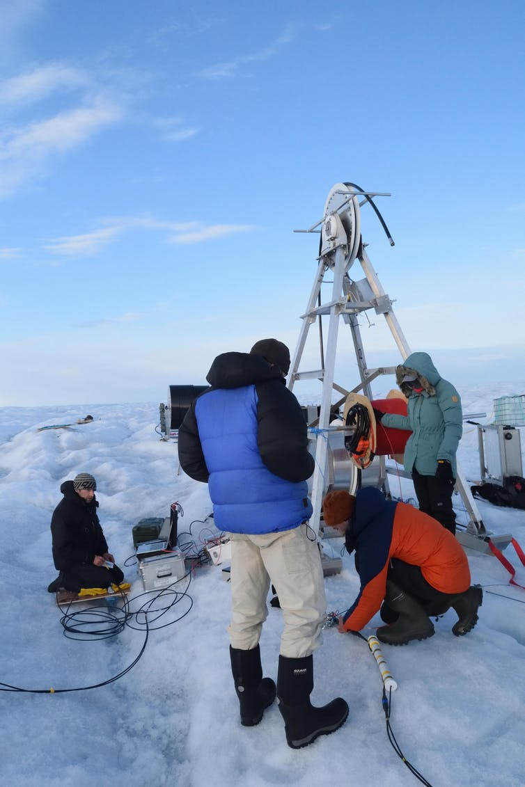 People stand around large equipment on an icy surface
