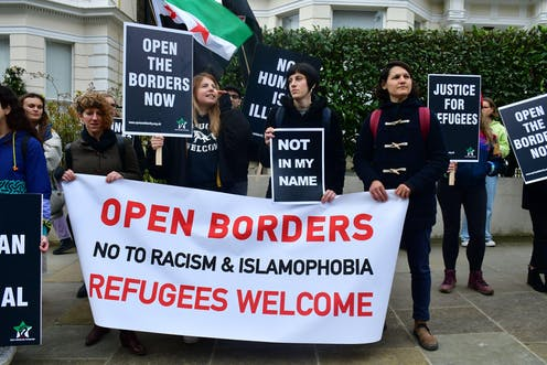 Protesters against Fortress Europe hold up banners demanding that borders be open and justice for refugees