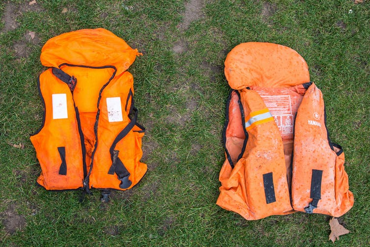 Two orange life jackets lie on the ground