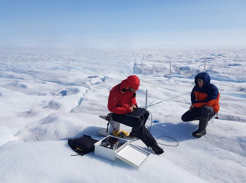 Scientists study equipment on an icy tundra