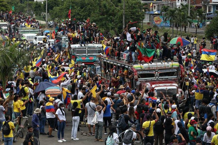 Des autobus remplis de manifestants circulent parmi la foule de marcheurs rassemblés dans les rue de Cali, en Colombie