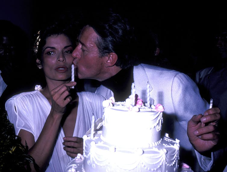 Halston kisses Bianca Jagger on the cheek behind her birthday cake.