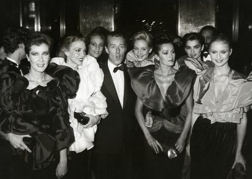 Halston poses with a group of elegantly dressed models.