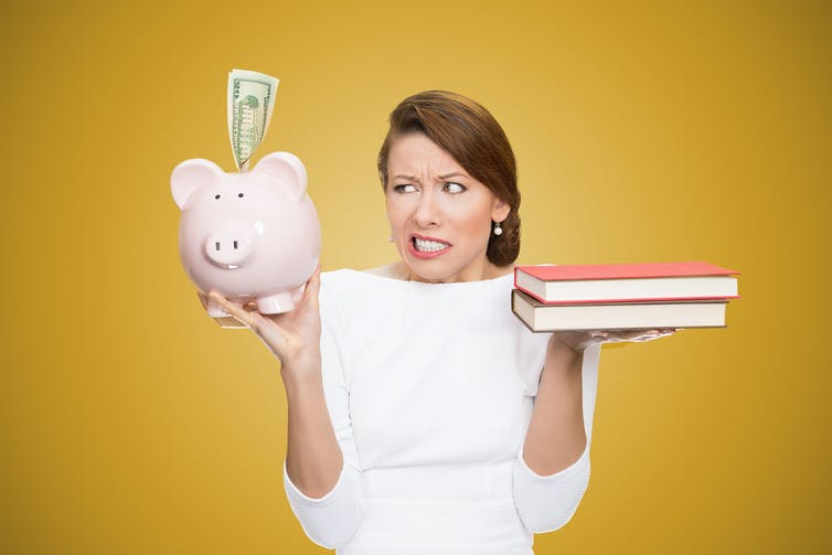 women weighs up books in one hand against piggybank in the other