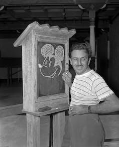 Man draws cartoon mouse on chalkboard