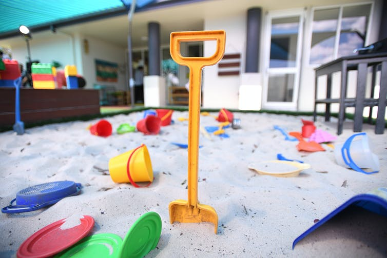 A sandpit with plastic toys (buckets and spades)