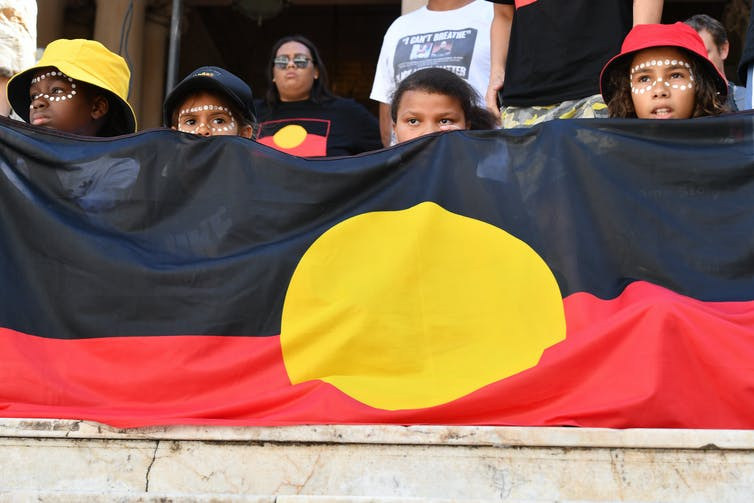Children hold an Indigenous flag at a Black deaths in custody rally.