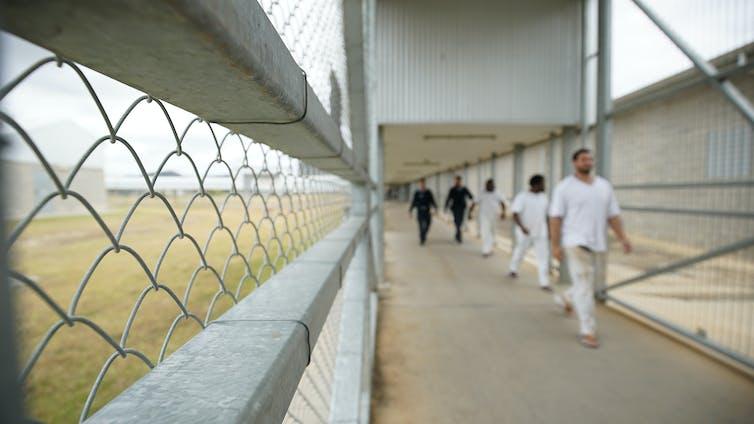 Staff escorting prisoners through a prison.