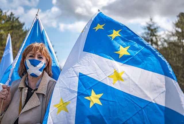 A woman waves a flag with EU stars superimposed on a Scottish saltire