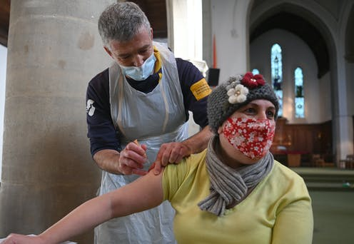 A woman in a face mask being vaccinated