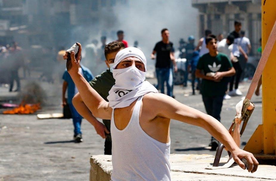 Un jeune Palestinien lance des pierres