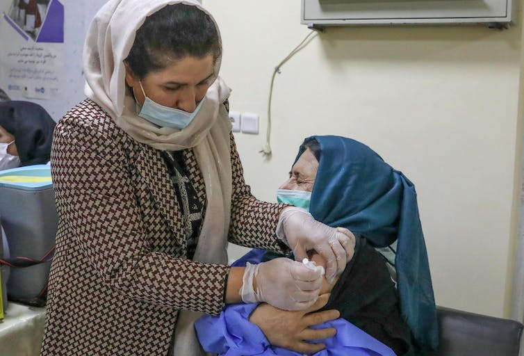 A health worker being vaccinated from COVID in Kabul, Afghanistan.