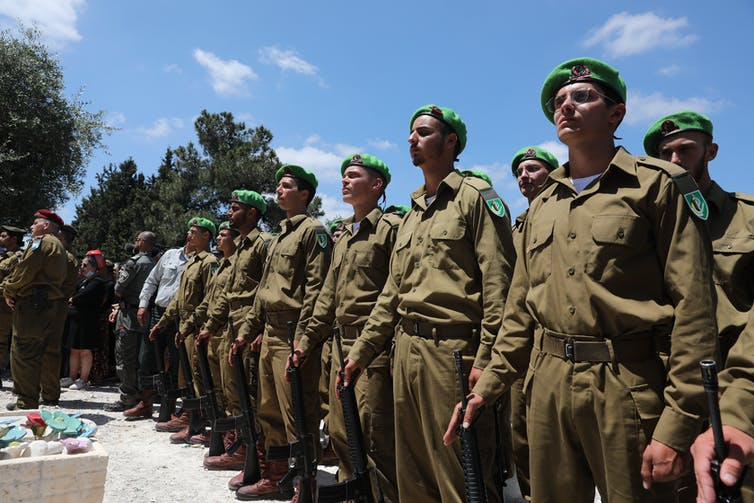 Israeli soldiers standing at attention over a coffin