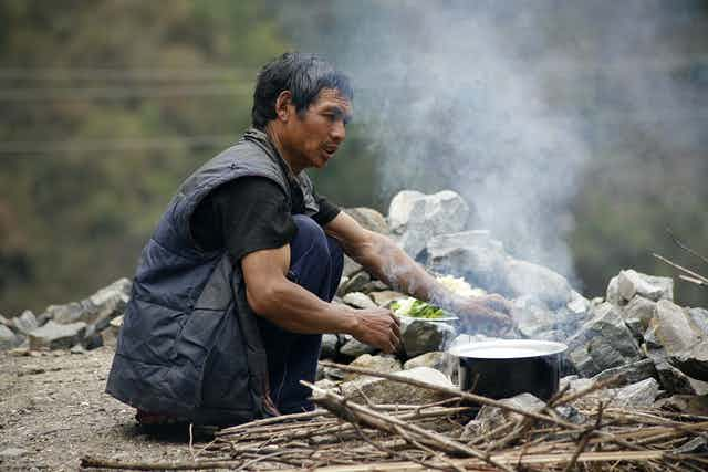 Man cooks over wood fire
