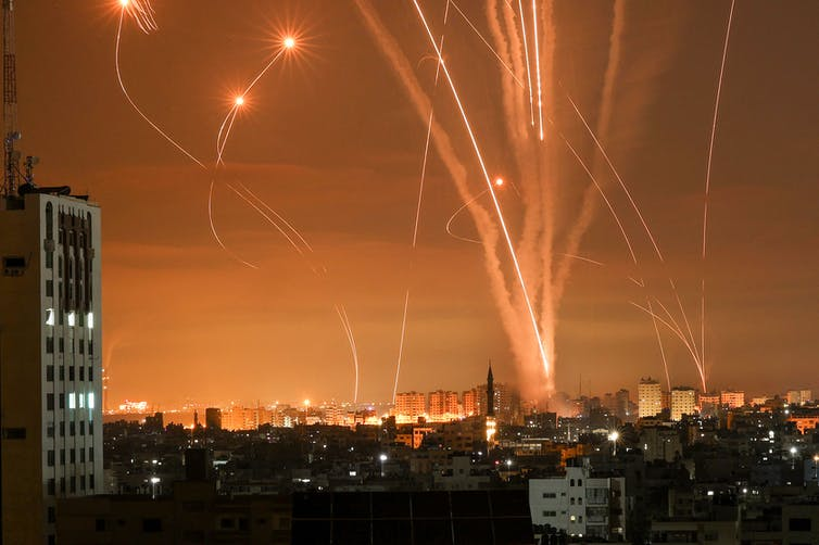 Bright trails of rockets fired towards Israel from the Gaza strip, lighting up the orange night sky