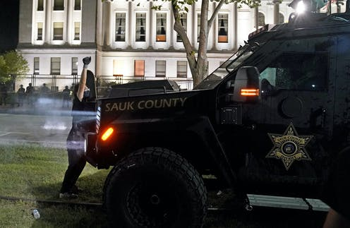 An armored vehicle with a sheriff's badge logo on the door moves toward a masked protester