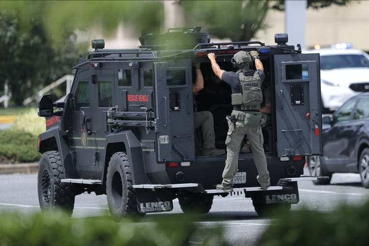 An armored vehicle drives with a helmeted man holding onto the back