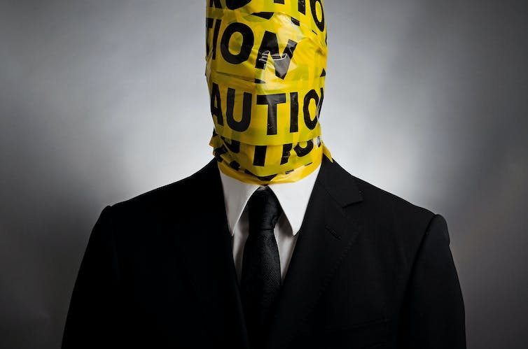 Man in a suit and tie with yellow police tape wrapped around his head and neck.