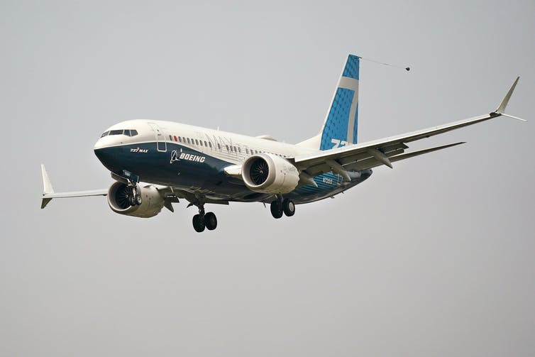 A twin-engine jetliner with its landing gear partway down and the name Boeing on the side descends through the air