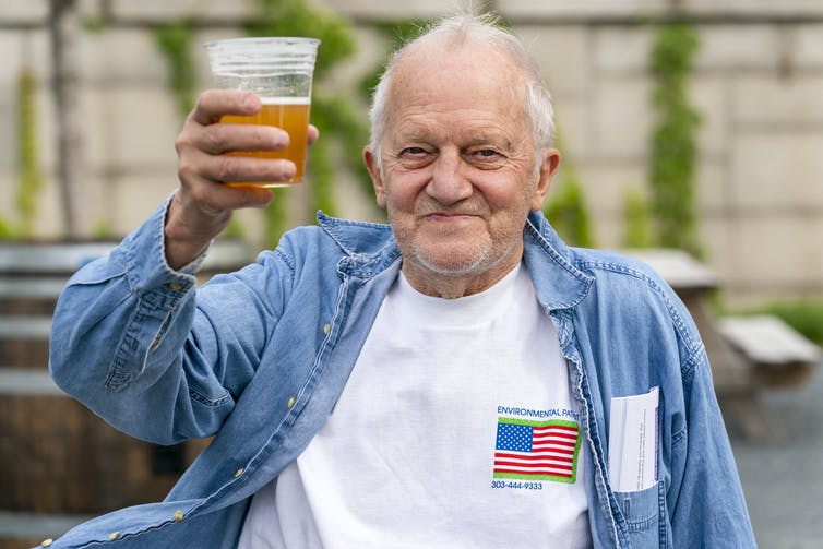 A man who just received a COVID-19 vaccine smiles as he holds up a cup with beer