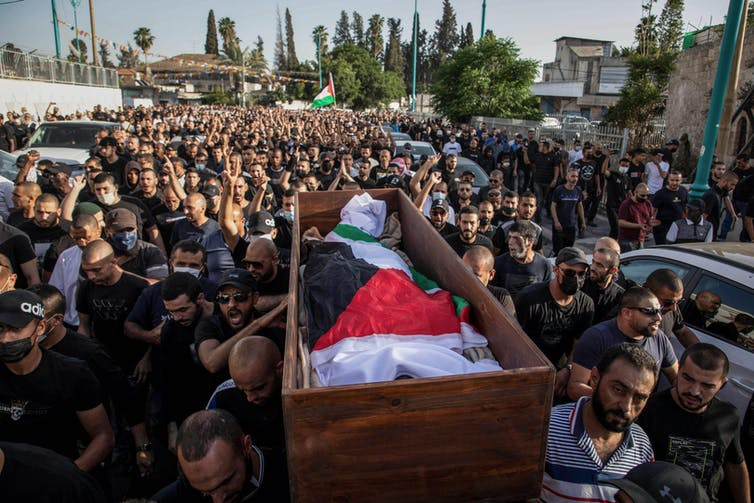 Arab Israeli men carry the body of a man wrapped in a Palestinian flag surrounded by crowds of people at a funeral
