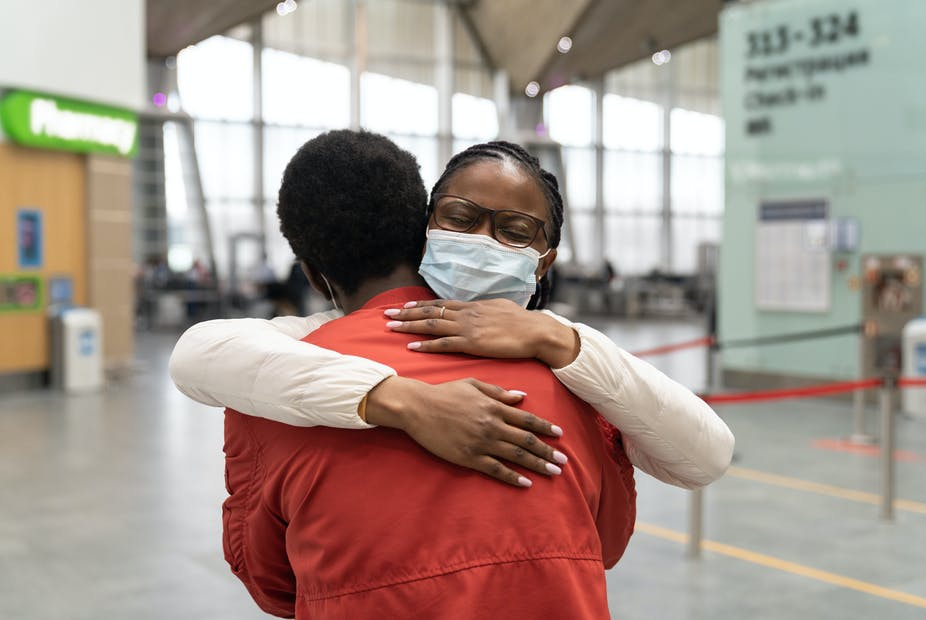 A woman wearing a face mask hugs a man in the airport.