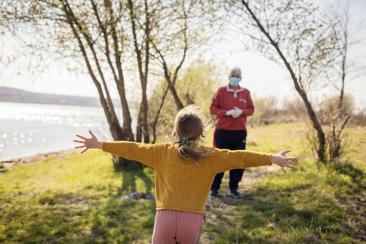 A young girl runs to hug her grandpa, who is wearing a mask outdoors.