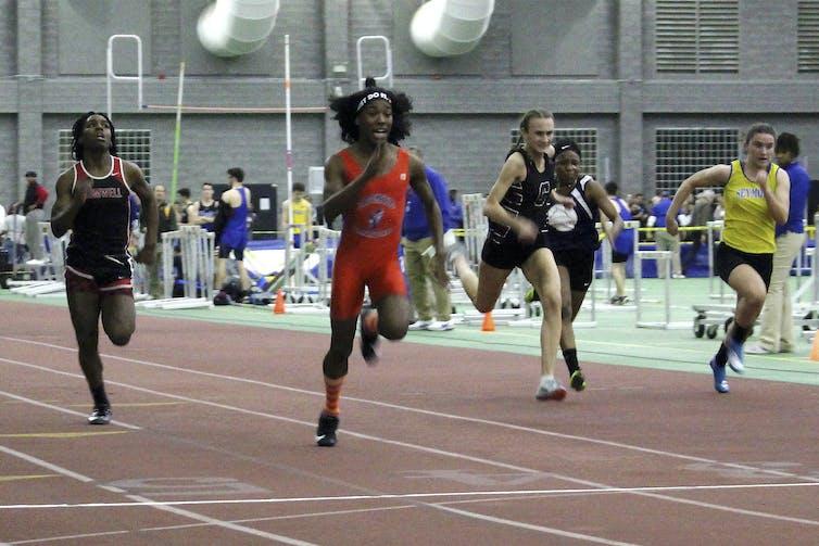 Four sprinters run at an indoor track meet.