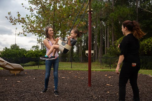 Trans mom and her wife push their child on a swing