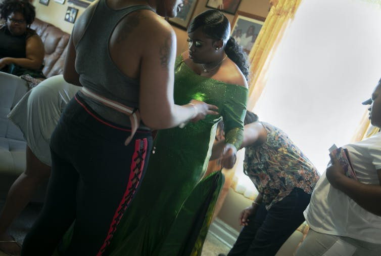 A young girl wearing an emerald dress prepares for prom with her family.