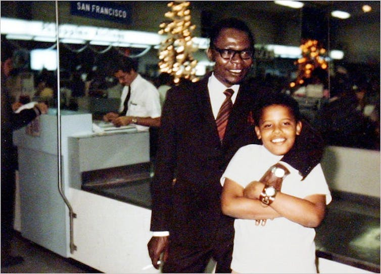 A man in a suit and tie poses with his arm around a young boy