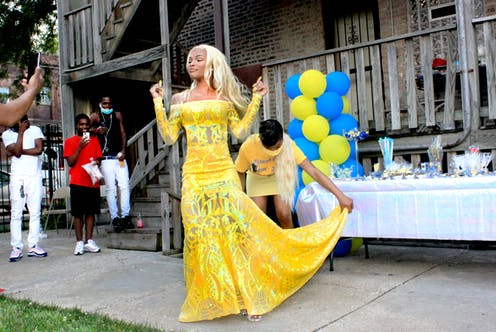 A young Black woman wears a yellow dress as a group of her siblings take photos of her.