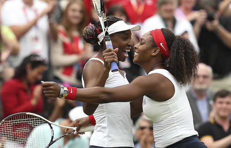 Serena and Venus Williams laugh on the tennis court.