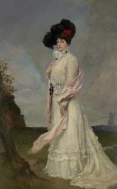 Full length portrait, Melba in a long white dress and big black hat.