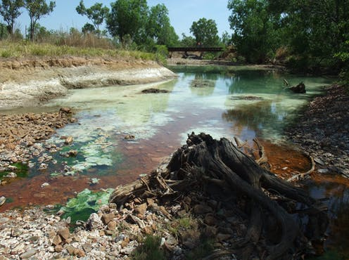 Red and green contaminated water in a river